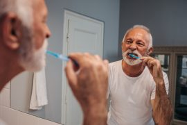 A person brushing his teeth with a toothbrush in his mouth Description automatically generated